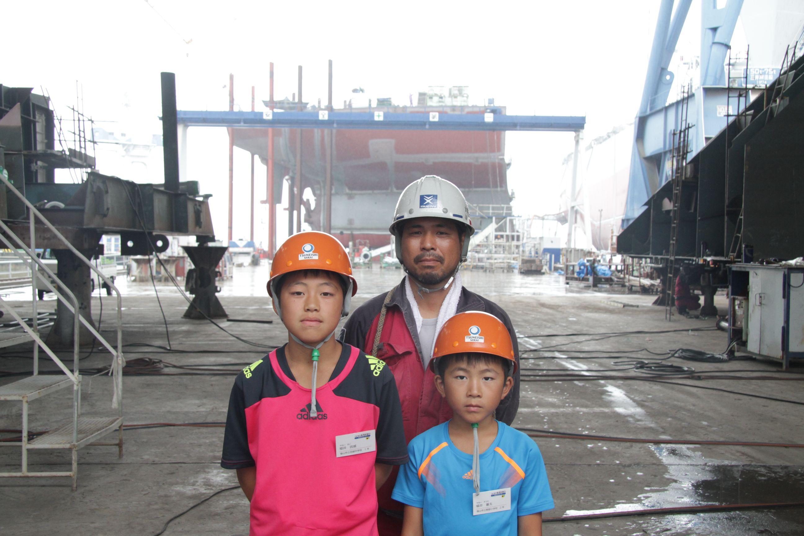 建造中の船をバックに親子で記念撮影