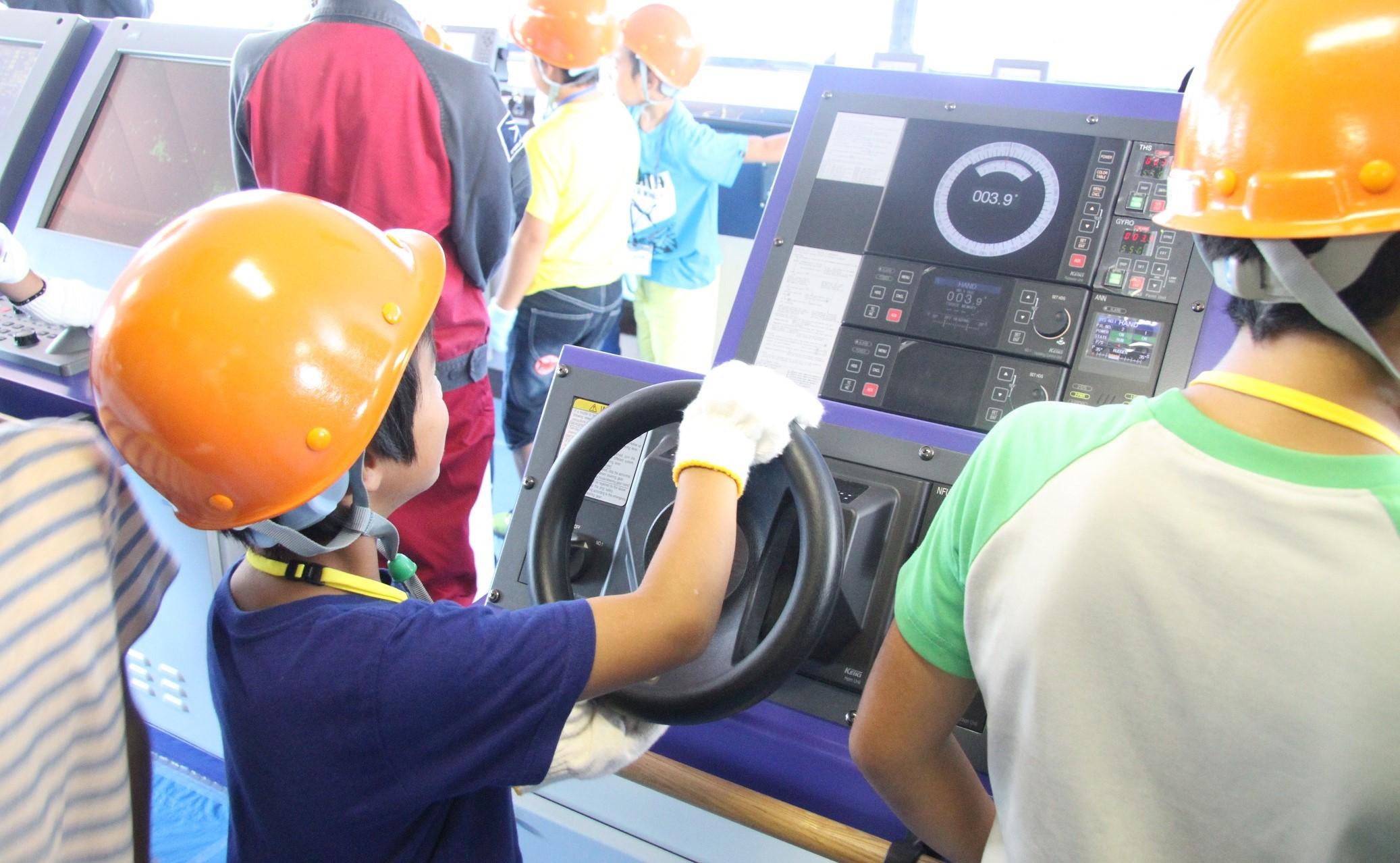 操縦室でステアリングホイールを握る子どもだち