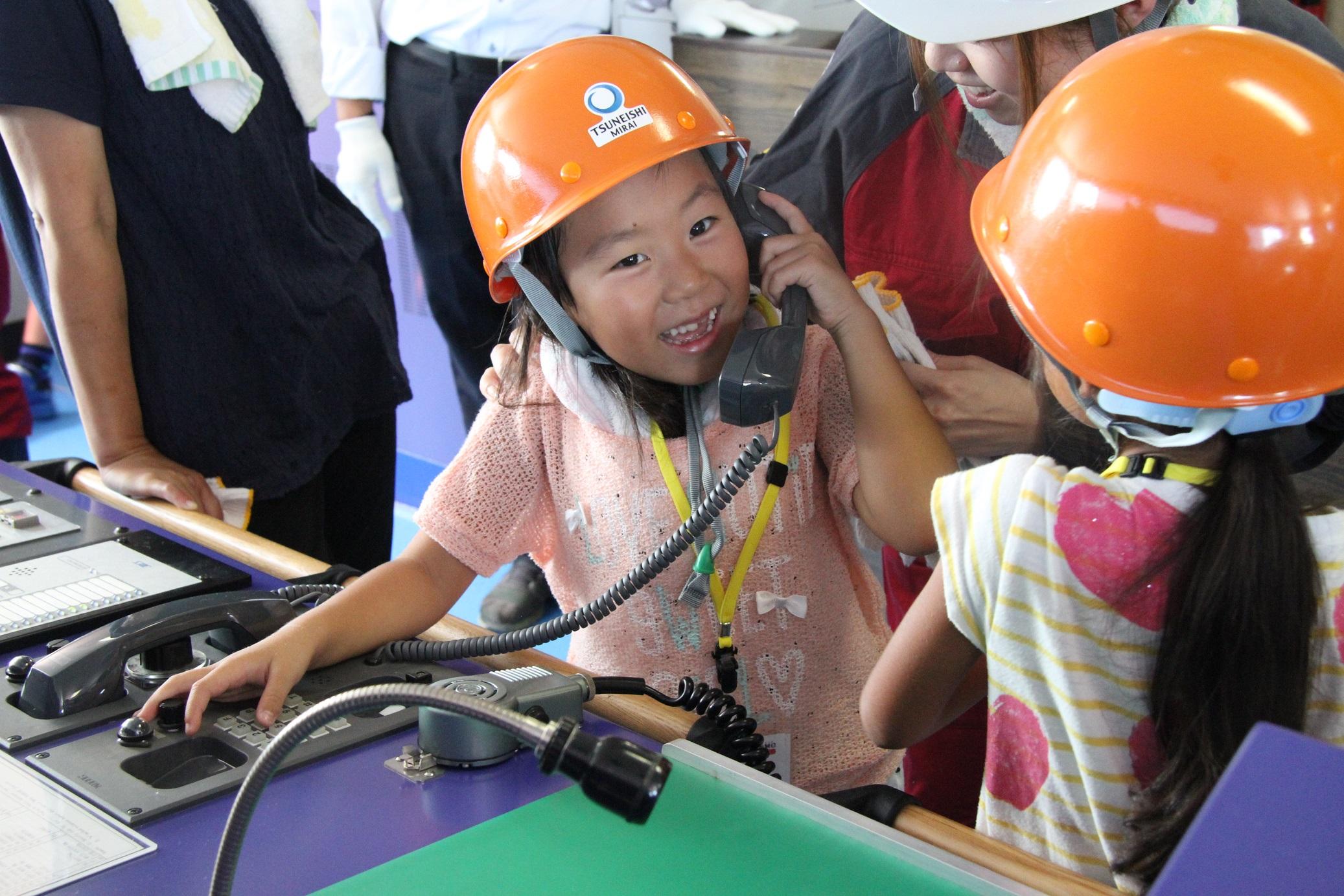 船内の通信機器を手に取る子どもたち